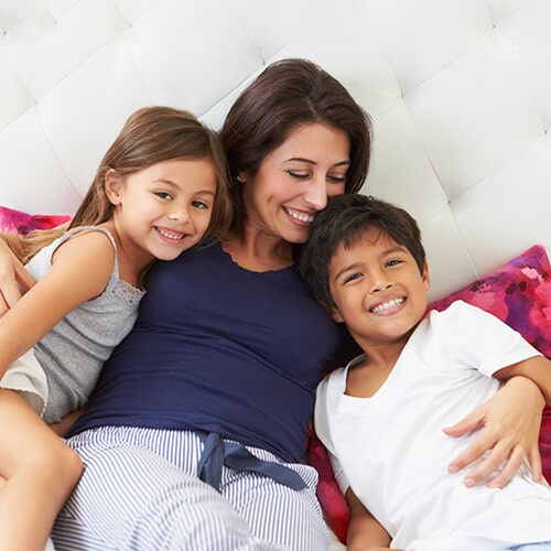 A mother sitting on a sofa while she hugs her son and daughter