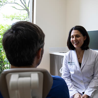 Dr. Fauzia Khan smiling while talking to one of our new patients