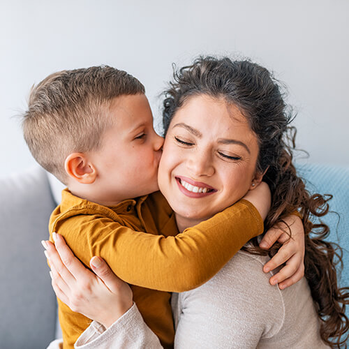 A young boy kissing his mother on the cheek at Lake Bluff Family Dentistry