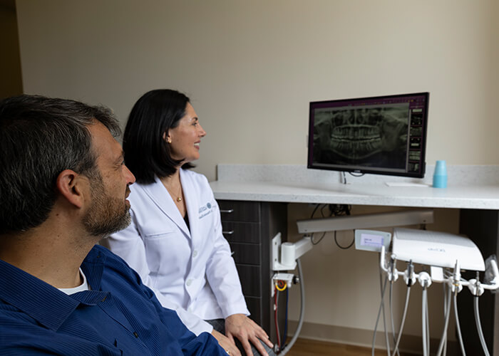 Dr. Khan with a Lake Bluff Family Dentistry patient looking at a monitor that shows digital x-rays