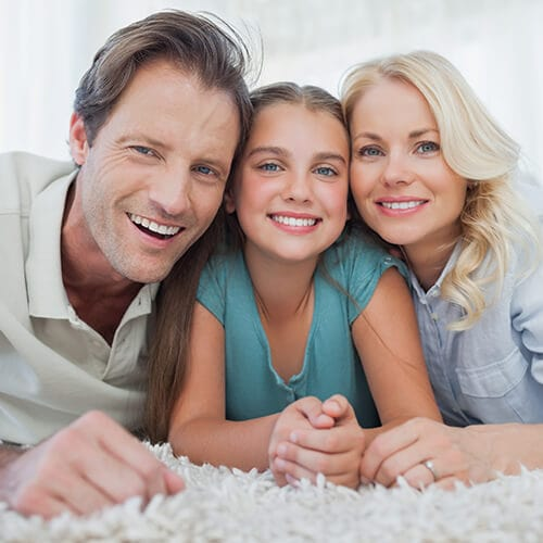 A family of three lying on the carpet while smiling together