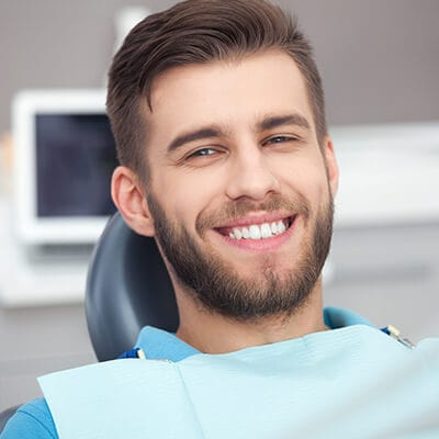 A man sitting in the dentist's chair while smiling and wearing a dental bib