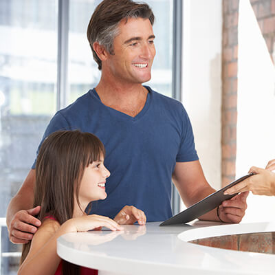 A dad and his daughter talking to the receptionist while handing them some forms