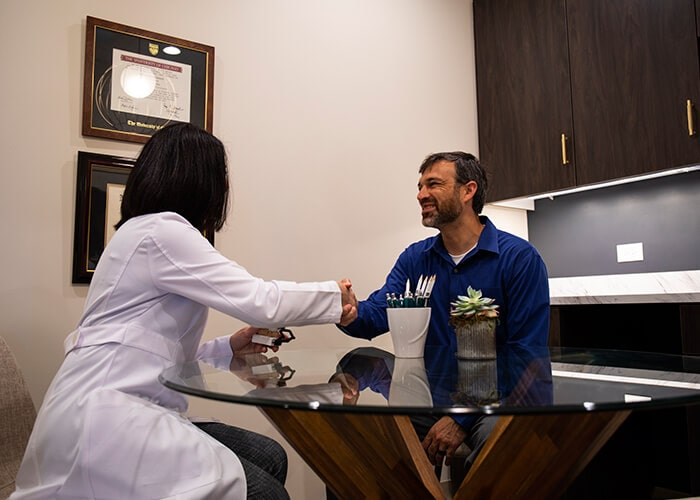 Dr. Fauzia Khan greeting a patient in the office while they are sitting at a circular glass table