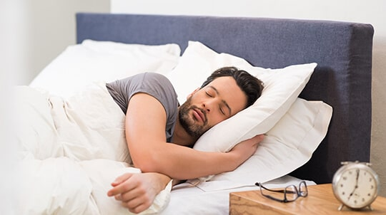 Man asleep in a bed after receiving cosmetic dentistry and airway therapy