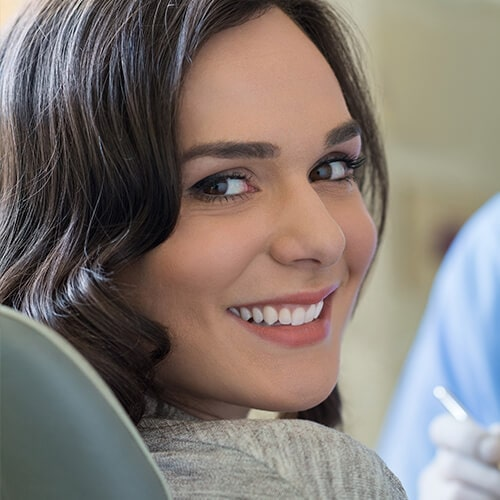 A young woman smiling sideways while in the dental office with the dentist