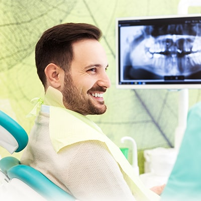 A man sitting in the dentist's chair while looking at an x-ray on a monitor