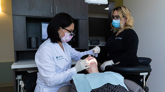 Dr. Khan and her assistant performing cosmetic dentistry on a female patient